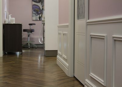 Chevron wooden floors leading down hallway of perio clinic