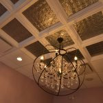 Lighting feature with metal circles surrounding crystal chandlier