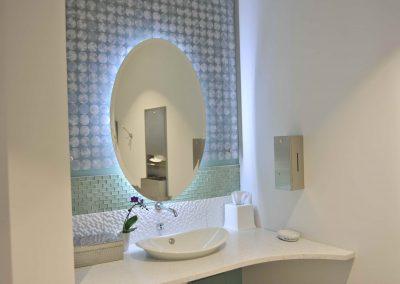 Backlit oval mirror in dental clinic bathroom