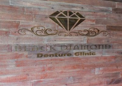 Custom logo built into wooden feature wall at dental clinic