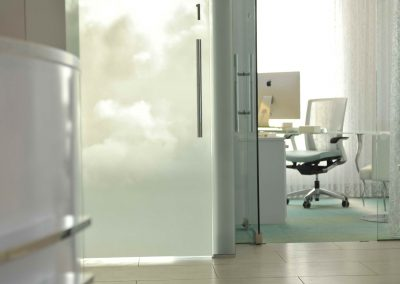 Glass sliding doors separating hallway of dental clinic and private offices
