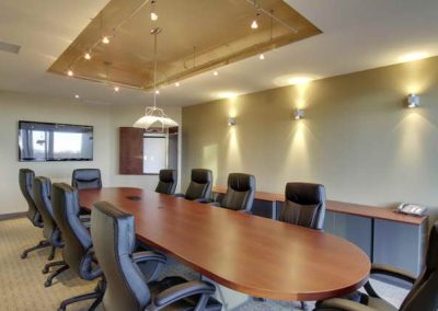 Large wooden boardroom table with leader rolling chairs placed around the table