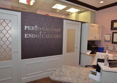 Purple damask wallpaper behind reception desk at perio clinic