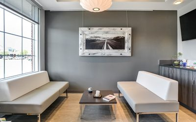 Two white and grey modern couches facing one another in waiting room
