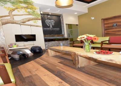 Waiting area in dental clinic with wooden floors and custom wooden table