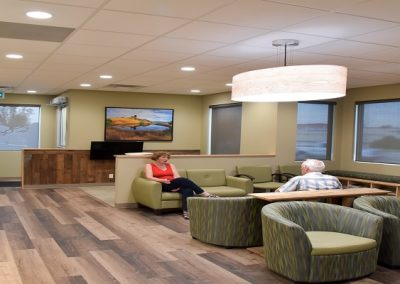 Large waiting room with wooden floors and large stone feature wall