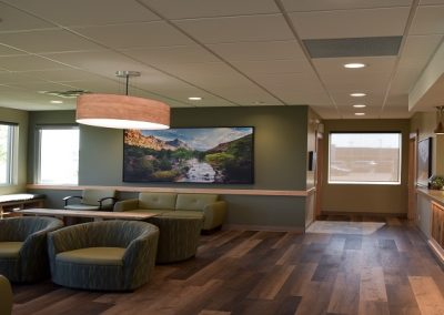 Large waiting room with green couches and wooden accents