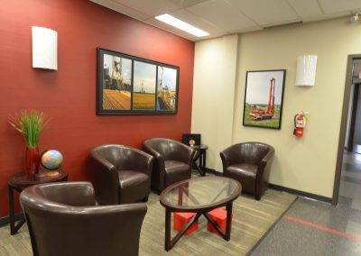 Commercial office waiting room with red feature wall and leather couches