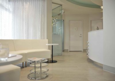 Modern seating area in dental clinic with angled white modern couches