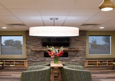 Large round feature light hanging up green couches in dental office waiting room