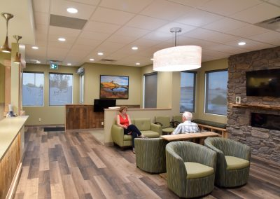 Dental waiting room designed with natural elements with wooden floor and stone fireplace