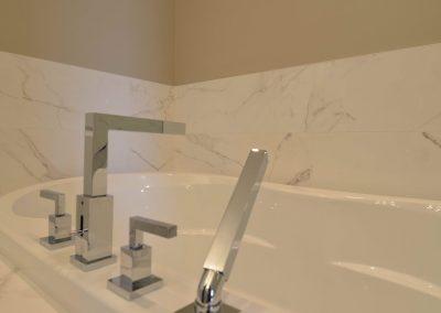 White tub with modern silver bathtub faucets