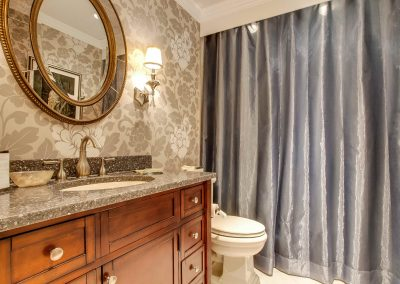 Gold floral wallpaper in bathroom with granite countertops
