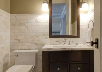Renovated powder room with white counter top and dark cabinets