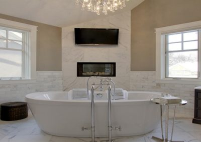 Large open concept master bathroom with white soaker tub and dark wooden vanities
