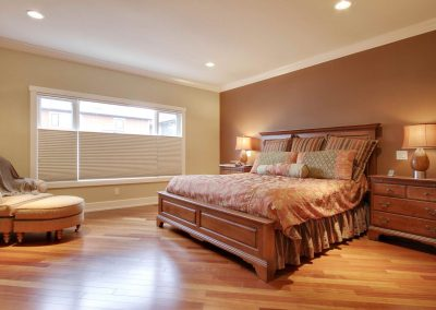 Master bedroom with kingside bed and wooden floors