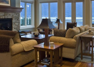 Living room area with lake view leading out to wrap around balcony
