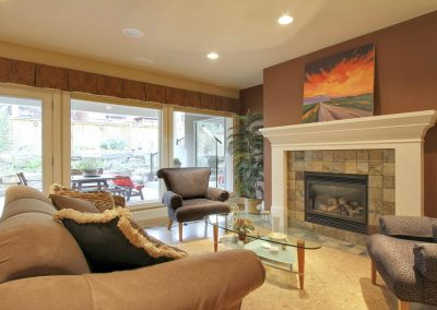 Family room seating area with furniture facing stone fireplace