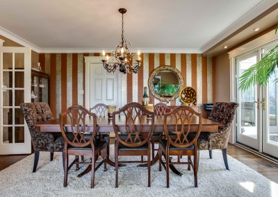 Dining room with large dining room table and a striped feature wall paper wall