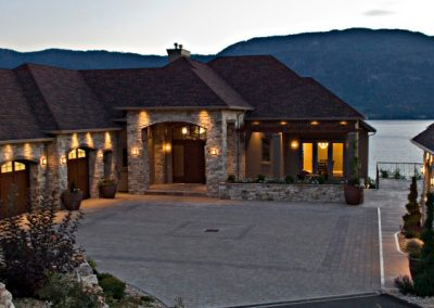 Custom home design with rock trim exterior and view of the lake