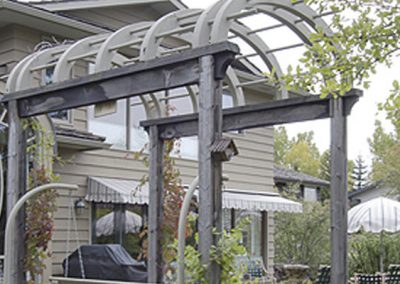 Arched pergola in backyard surrounded by trees