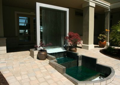 Custom outdoor water feature flowing into pond