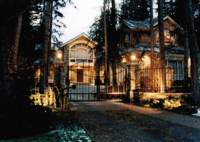 Driveway leading up to gated house surrounded by forest