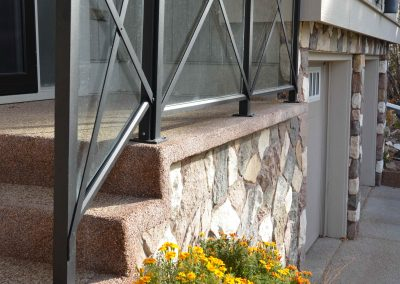 Glass railing leading up steps into house