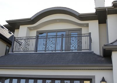 Arched roof above master bedroom balcony with black railings