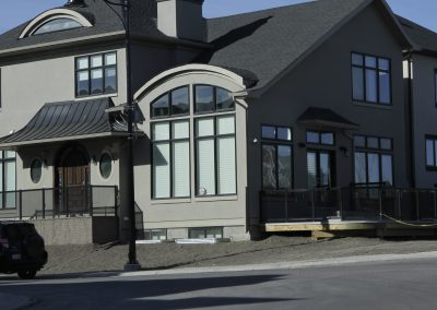 New custom home with large arching windows and black trim
