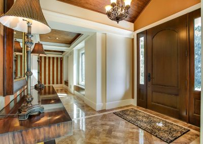 Front entryway of home with marble floors and large table with lamps