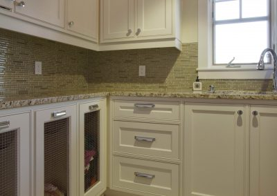 Renovated laundry room with built in sliding laundry bins