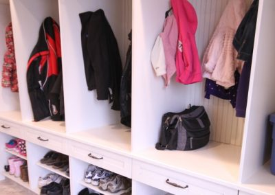 White mudroom with hanging areas and white drawers and shoe holders