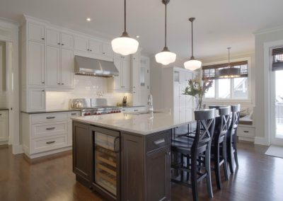 White themed kitchen renovation with contrasting dark wooden island
