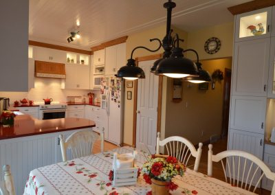 Country style kitchen with white ceilings and red accents on counters