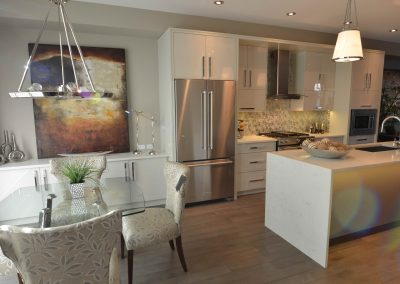 White modern kitchen renovation with glass table, white features and a long white island