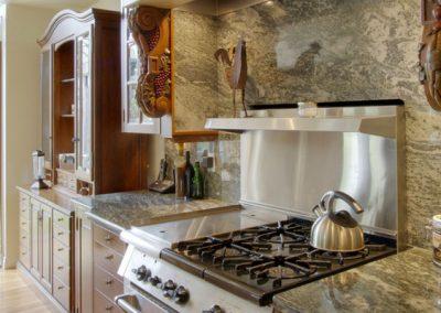 Granite backsplash surrounding stainless steel oven top