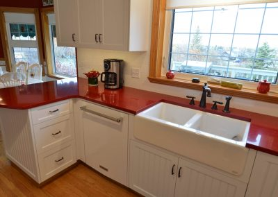 Farmhouse kitchen sink and red countertops