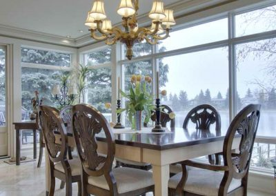 Eleganat styled dining room table surrounded by floor to ceiling windows