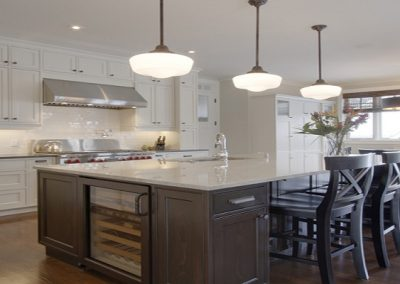 Custom kitchen island design with bar chairs and built in wine fridge