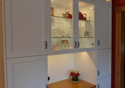 Built in kitchen desk surrounded by custom white kitchen cabinets