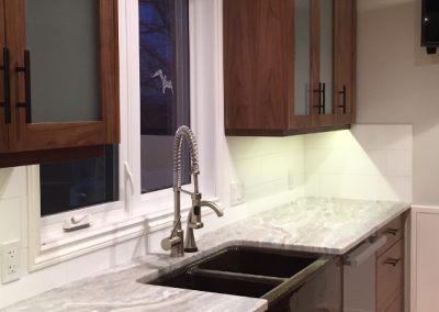 modern kitchen with dark brown cabinets and a deep black granite kitchen sink