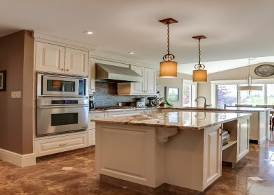 open concept kitchen with marble floors and large white island in middle of kitchen