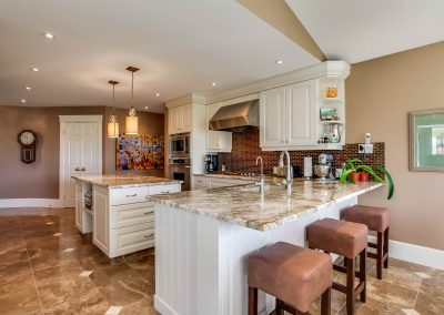 Quartz countertops with white wooden elements throughout kitchen