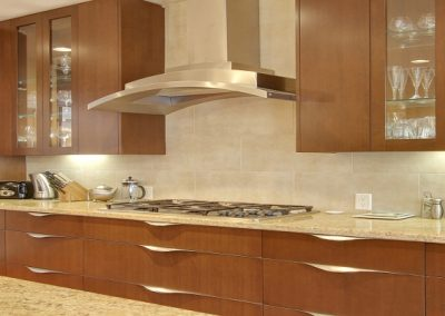 Arched hood fan and white granite kitchen top with custom wooden drawers